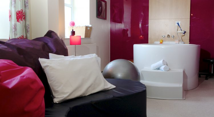 Photo of a birthing room at a birth unit, shows pool, birthing ball and couch