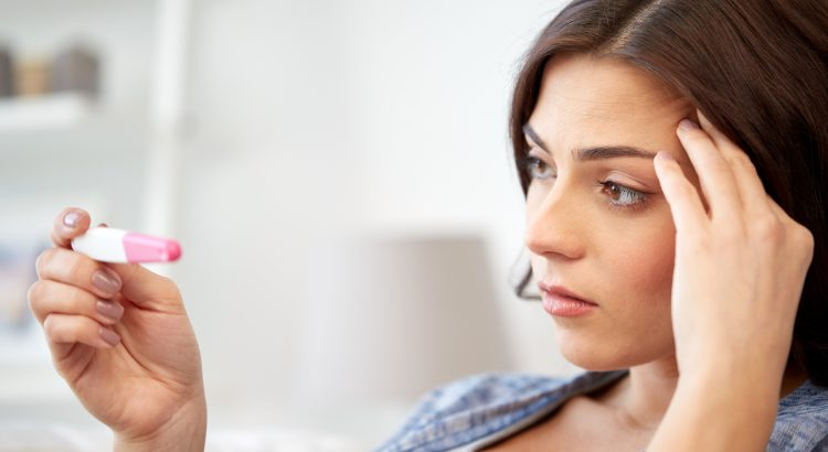 Woman holding a pregnancy test and looking anxious.